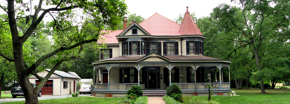 Large house with red tin shingle roof, wrap-around porch and many shuttered windows with brick walkway lined with hedges