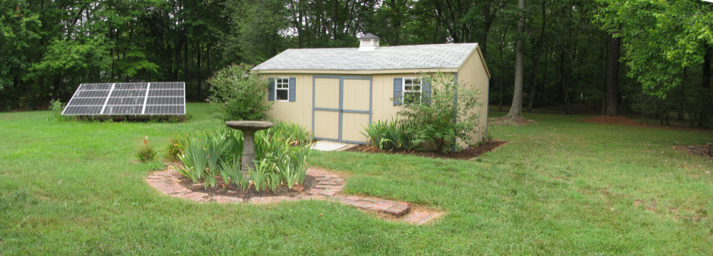 Amish-made modern shed with same style and coloring of house in beautiful green lawn with solar panel to the far side