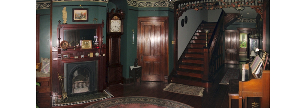 dark wook on doors, stairs, grandfather clock, fireplace, and picture rail with walls painted dark green and victorian wall paper trim