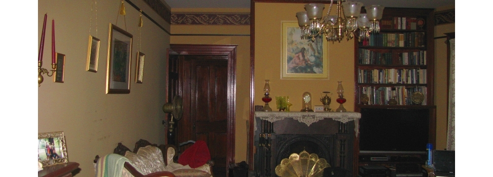 Gold painted walls with Victorian decor and black flat screen tv in book shelf next to fireplace